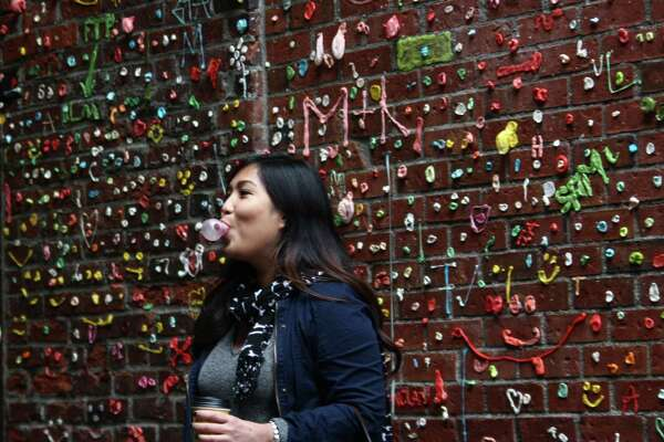 Danica Legaspi, of Las Vegas, poses chewing a big piece of gum Monday morning, while her friend Erwin Dizon takes a photo before they both stuck their gum — bought just for the purpose — into Seattle's recently cleaned gum wall. The wall, in Post Alley near Pike Place Market, was cleaned last week for the first time in 20 years. It didn't stay clean for long, though, as visitors had already begun re-gumming the brick wall over the weekend. DANIEL DEMAY/SEATTLEPI.COM