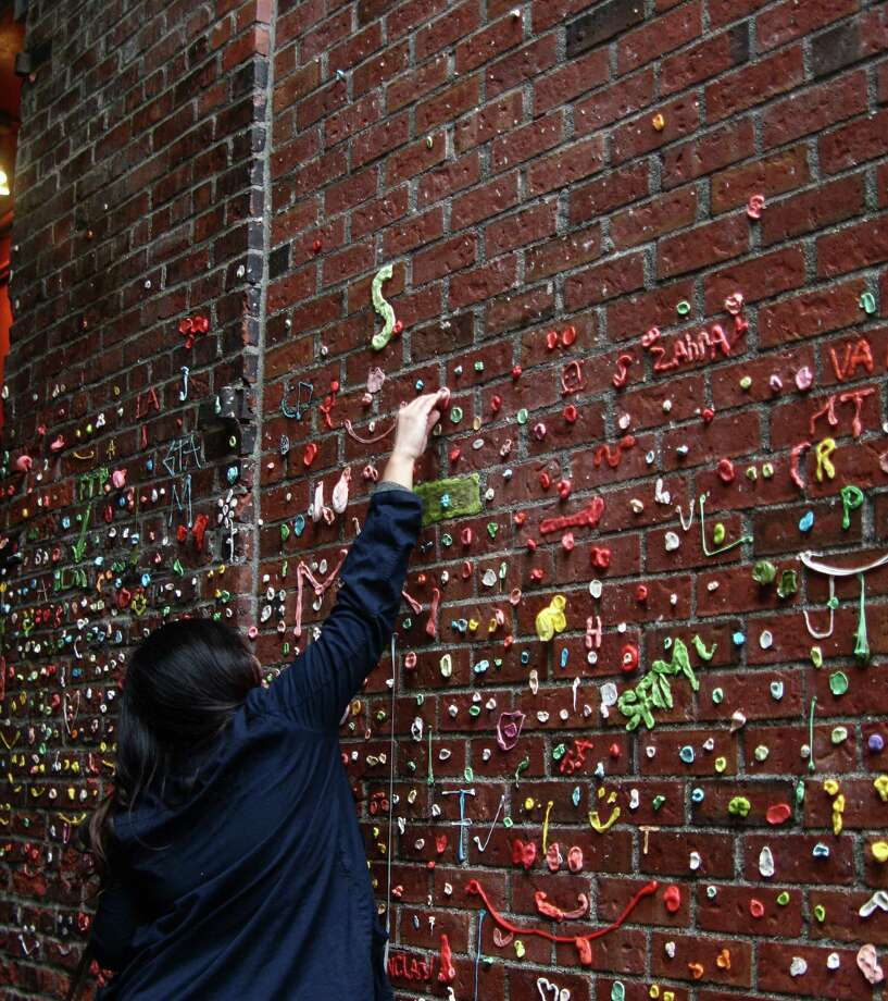 Danica Legaspi, of Las Vegas, on Monday makes sure her freshly chewed gum sticks to the recently cleaned gum wall. Her and her friend Erwin Dizon got to town last week just as the cleaning was getting underway, much to their chagrin, they said. Seattle's famous gum wall, in Post Alley near Pike Place Market, was cleaned last week for the first time in 20 years. It didn't stay clean for long, though, as visitors had already begun re-gumming the brick wall over the weekend. DANIEL DEMAY/SEATTLEPI.COM Photo: DANIEL DEMAY/SEATTLEPI.COM