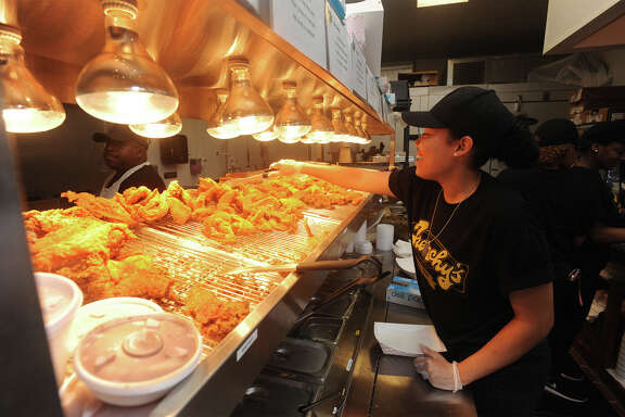 A three-piece meal served with beans and rice at Frenchy's Chicken. Jameir Quintanilla prepares chicken lunches Wednesday at Frechy's in Beaumont's College Street H-E-B. Photo taken Wednesday, June 17, 2015 Guiseppe Barranco/The Enterprise   Manditory Credit, No Sales, Mags Out, TV Out, Web: AP Members only