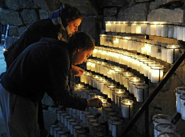 Siena seniors Marie Tetard, 23, of Paris, France, left, and Debra Johnson, 21, of Long Island light candles in the campus grotto as Siena College hosted a vigil on Monday, Nov. 16, 2015, in Loundonville, N.Y., for the victims of the Paris attacks on Friday. Tetard did not know any of the victims personally. (Lori Van Buren / Times Union) Photo: Lori Van Buren / 00034287A