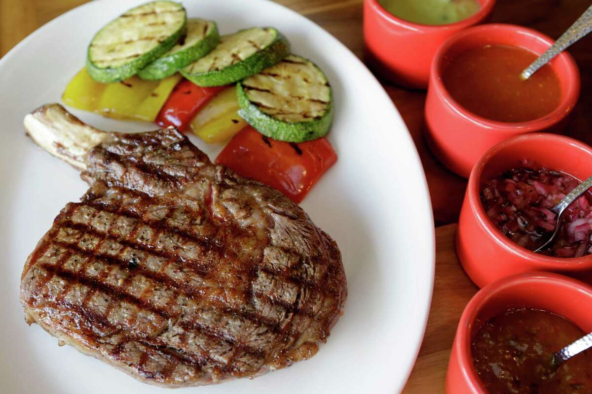 A cowboy bone-in rib-eye with grilled vegetables is served along with four salsas at Saltillo Mexican Kitchen.