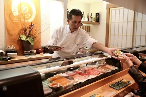 Owner-chef Kiyoshi Hayakawa serves sushi to guests at An Japanese restaurant for dinner in San Francisco, California, on Friday, November 13, 2015.