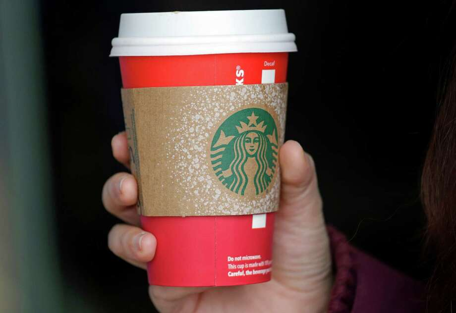 A customer carries a coffee drink in a red paper cup, with a cardboard cover attached, outside a Starbucks coffee shop in the Pike Place Market, Tuesday, Nov. 10, 2015, in Seattle. It's as red as Santa's suit, a poinsettia blossom or a loud Christmas sweater. Yet Starbucks' minimalist new holiday coffee cup has set off complaints that the chain is making war on Christmas. (AP Photo/Elaine Thompson) Photo: Associated Press / AP