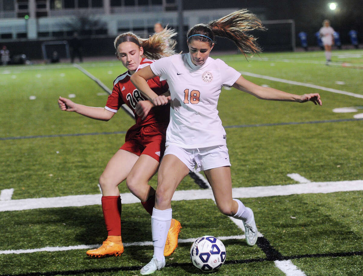 New Canaan's Brooke Volpe, left, and Ridgefield's Molly Nethercott play the ball during their Class LL girls soccer semifinal game at Ludlowe High School in Fairfield Monday.