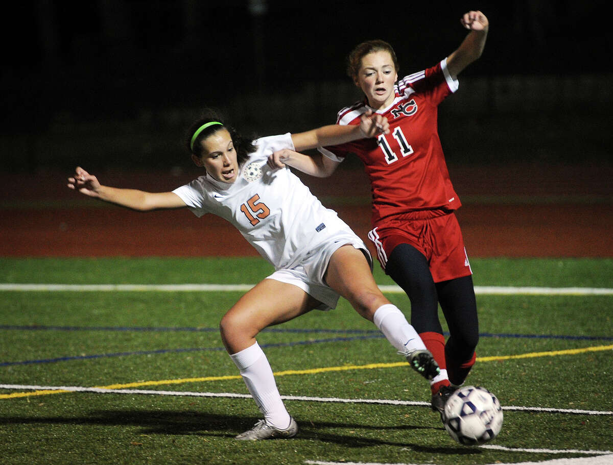 Ridgefield's Alyssa Bonanno, left, battles for the ball with New Canaan's Kelly McClymonds during their Class LL girls soccer semifinal game at Ludlowe High School in Fairfield, Conn. on Monday, November16, 2015.