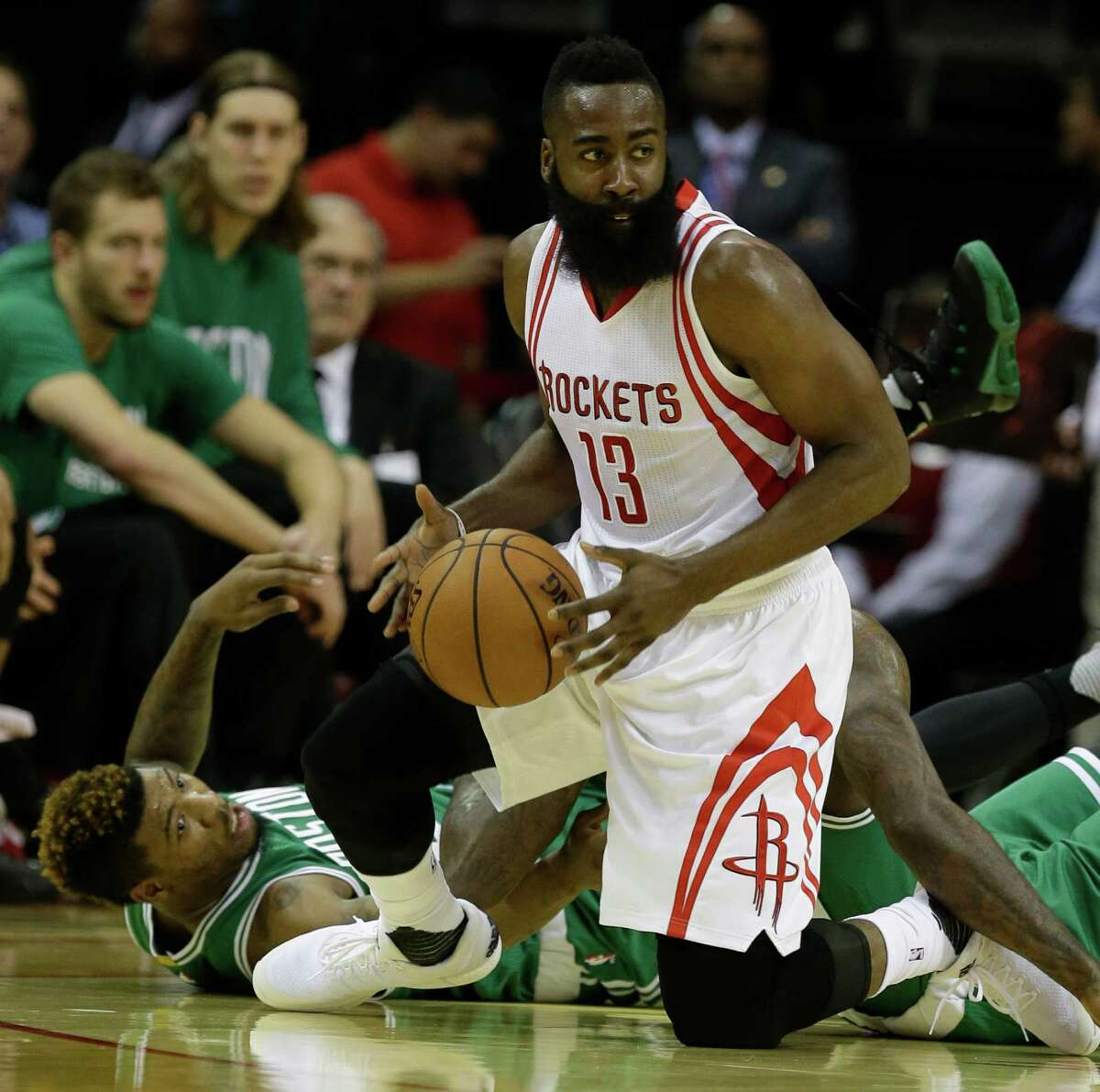 Rockets guard James Harden comes up with ball after getting the better of a floor scramble with the Celtics' Marcus Smart during the first half of Monday's game.