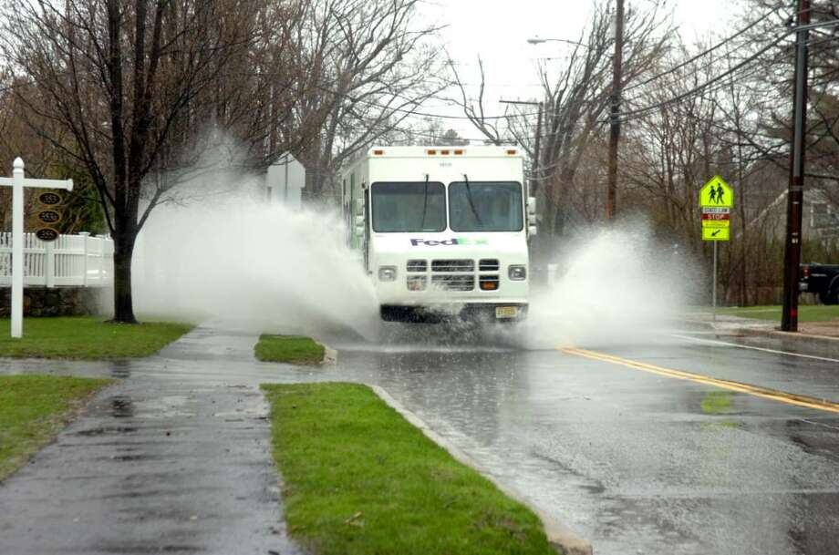 An FedEx truck steams through a large puddle on Sound Beach Avenue, on Monday, March 29, 2010. Photo: Helen Neafsey / Greenwich Time