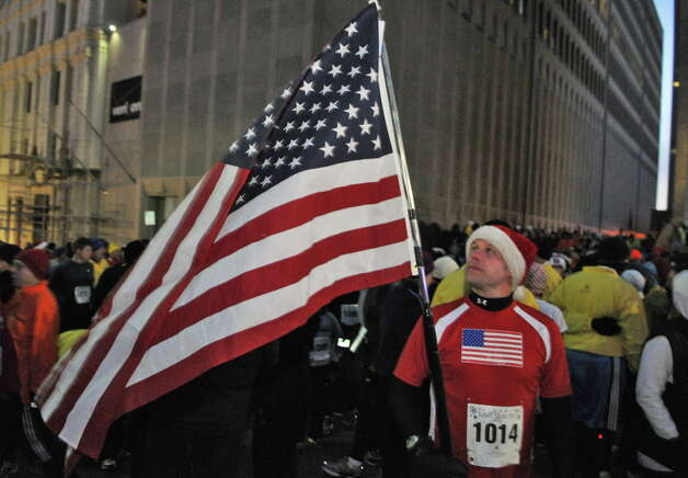 """Miles 4 Vets"" runner Robert Smith of East Berne unfurls an American flag at the start of the 15th Annual Last Run 5K  race in Albany Saturday Dec. 17, 2011.    (John Carl D'Annibale / Times Union) Photo: John Carl D'Annibale / 00015785A"