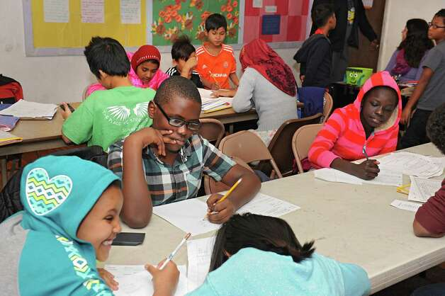 Children work on homework during an after-school program for refugee children at the Refugee and Immigration Support Services of Emmaus (RISSE) classroom on Monday, Nov. 9, 2015 in Albany, N.Y.  (Lori Van Buren / Times Union) Photo: Lori Van Buren / 00034133A