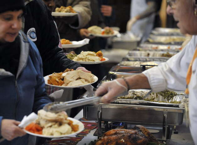 Volunteers dish out food to guests at last year's Equinox Thanksgiving Community Dinner at the First Presbyterian Church in Albany. (Paul Buckowski / Times Union)