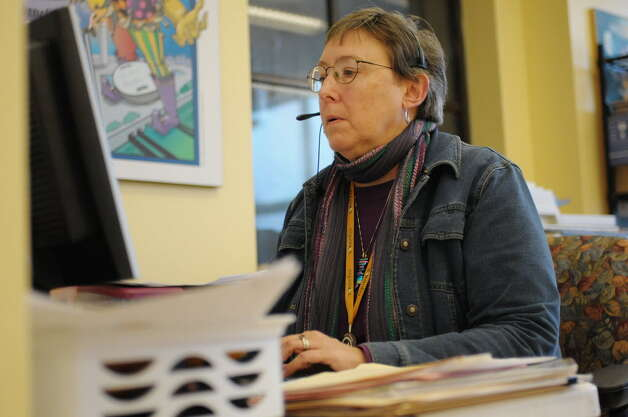 Nancy Virkler, the hot line coordinator at Equinox, works at her desk at the nonprofit's downtown Albany offices. (Paul Buckowski / Times Union)