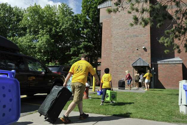 Siena College tour guides, resident advisors, admission staff and orientation leaders carry a new student's belongings into a dorm as freshmen students moved in to their campus housing on Thursday, Aug. 28, 2014, in Loudonville, N.Y.    (Paul Buckowski / Times Union) ORG XMIT: MER2014082815275476 Photo: Paul Buckowski / 00028227A