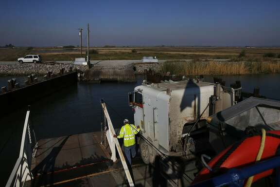Larry Etherton prepares to unload a massive transport truck from a ferry on Middle River that will be filled with corn on Webb Tract Island Nov. 13, 2015 near Rio Vista, Calif. Webb Tract Island is one of two Islands that Barajas manages for a local farmer. Barajas lives on Bouldin Island.