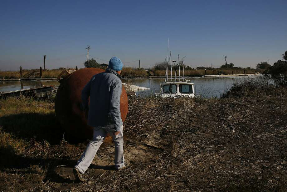 Above: John Sweeney heads for a boat on Chipps Island near Pitts burg. Chipps, in the Suisun Marsh, is also used for duck hunting. Photo: Leah Millis, The Chronicle