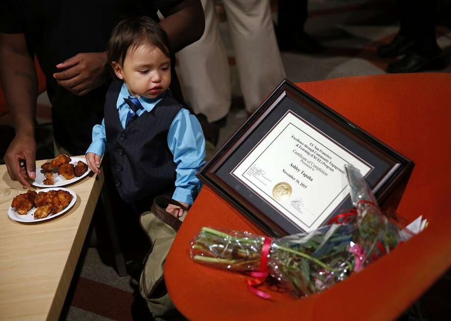 Alonzo Hernandez, 1, looks at his mother Ashley Tapaha's EXCEL graduation certificate of completion after ceremony at Genentech Hall on UCSF's Mission Bay campus in San Francisco, Calif., on Monday, November 16, 2015. Photo: Scott Strazzante, The Chronicle
