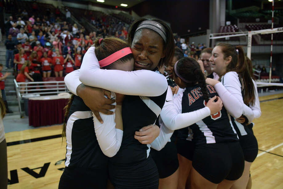 Fort Bend Austin senior middle blocker Madison Rhoder, center, shares a hug with teammate and senior outside hitter Paige Swinney, left, after their 5-game win over the Seven Lakes Spartans in their Class 6A Region III volleyball championship at the Campbell Center in Houston on Saturday, Nov. 14, 2015. Photo: Jerry Baker, Freelance