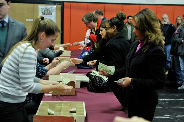 People purchase rolls of the new quarters during an event by the U.S. Mint to unveil the coin honoring Saratoga National Historical Park on Tuesday, Nov. 17, 2015, at Schuylerville High School in Schuylerville, N.Y.  The new coin is part of the U.S. Mint's America the Beautiful Quarters Program.  (Paul Buckowski / Times Union) Photo: PAUL BUCKOWSKI / 00034051A