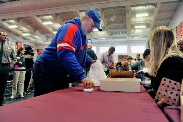 Rit Bietka from Ballston Spa purchases rolls of the new quarter during an event by the U.S. Mint to unveil the coin honoring Saratoga National Historical Park on Tuesday, Nov. 17, 2015, at Schuylerville High School in Schuylerville, N.Y.  The new coin is part of the U.S. Mint's America the Beautiful Quarters Program.  (Paul Buckowski / Times Union) Photo: PAUL BUCKOWSKI / 00034051A