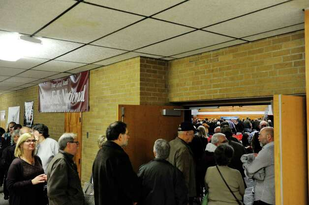 People stand in a long line leading into the gym to purchase rolls of the new quarters during an event by the U.S. Mint to unveil the coin honoring Saratoga National Historical Park on Tuesday, Nov. 17, 2015, at Schuylerville High School in Schuylerville, N.Y.  The new coin is part of the U.S. Mint's America the Beautiful Quarters Program.  (Paul Buckowski / Times Union) Photo: PAUL BUCKOWSKI / 00034051A
