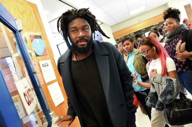 Jason Reynolds of Brooklyn, an award-winning writer of young adult books, center, walks though the hallway on Tuesday, Nov. 17, 2015, at Albany High in Albany, N.Y. Reynolds was at the high school to share his books and life story to student. (Cindy Schultz / Times Union) Photo: Cindy Schultz / 00034265A