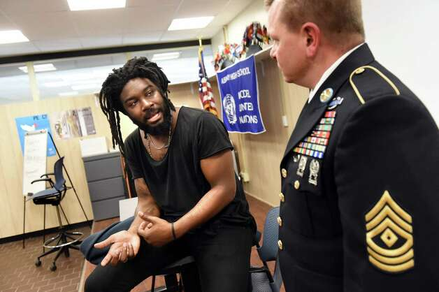 Jason Reynolds of Brooklyn, an award-winning writer of young adult books, left, talks with 1st Sgt. Dennis Palow, JROTC commanding officer, on Tuesday, Nov. 17, 2015, at Albany High in Albany, N.Y. Reynolds was at the high school to share his books and life story to student. (Cindy Schultz / Times Union) Photo: Cindy Schultz / 00034265A