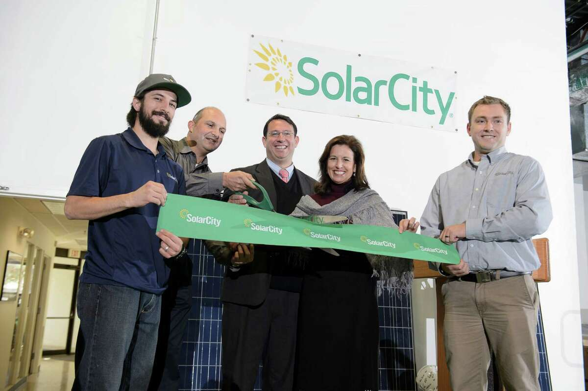 SolarCity's Mike Brignano, Lee Keshishian and Chris Scott, along with state Sen. Gayle Slossberg and Milford Mayor Ben Blake, center, cut the ribbon on the company's operations center in Milford.