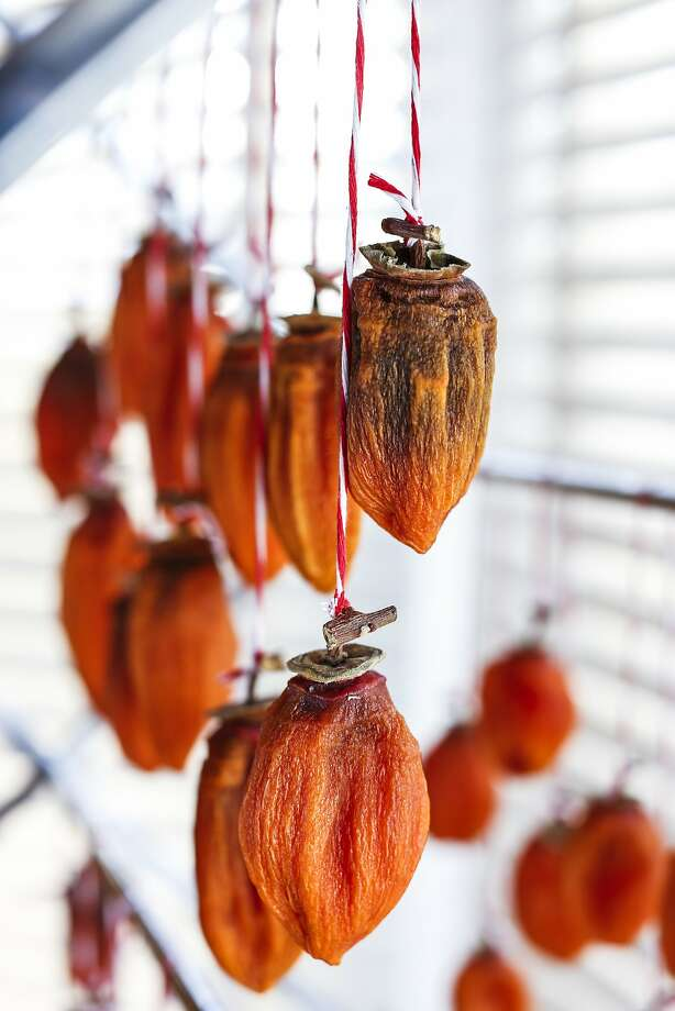 Resembling colorful lanterns, persimmons air dry in chef Bruce Hill's home kitchen for hoshigaki. Photo: Russell Yip, The Chronicle