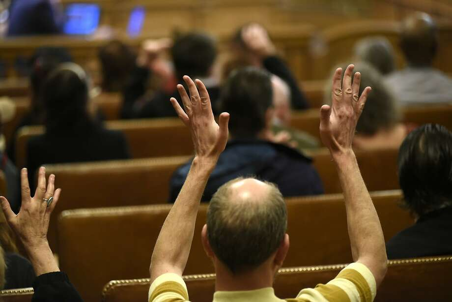 Members of the public wave their hands in support of a speaker speaking against the 5M project during a board of supervisors meeting at City Hall in San Francisco, CA Tuesday, November 17 2015. Photo: Michael Short, Special To The Chronicle
