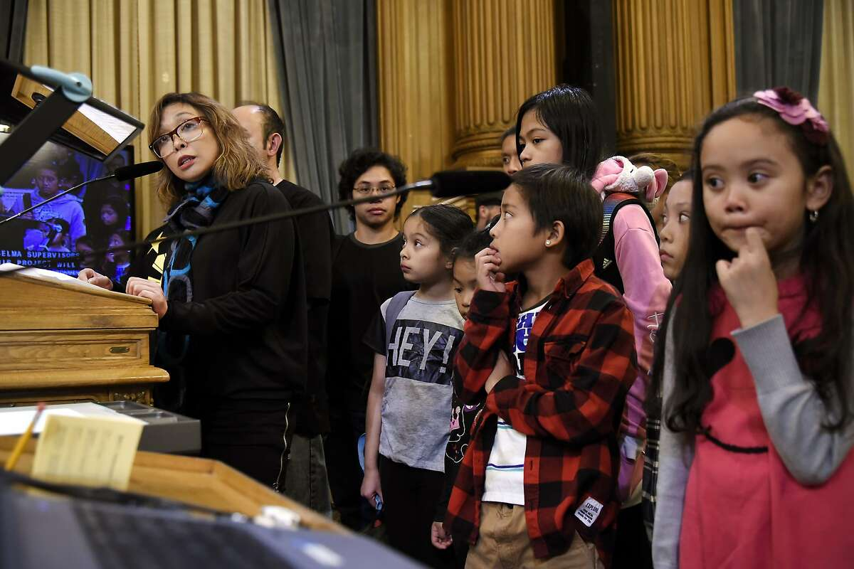 Executive director of West Bay Pilipino Vivian Zalvidea Araullo, left, stands with Filipino youth from her program as she speaks against the 5M project during a board of supervisors meeting at City Hall in San Francisco, CA Tuesday, November 17 2015.