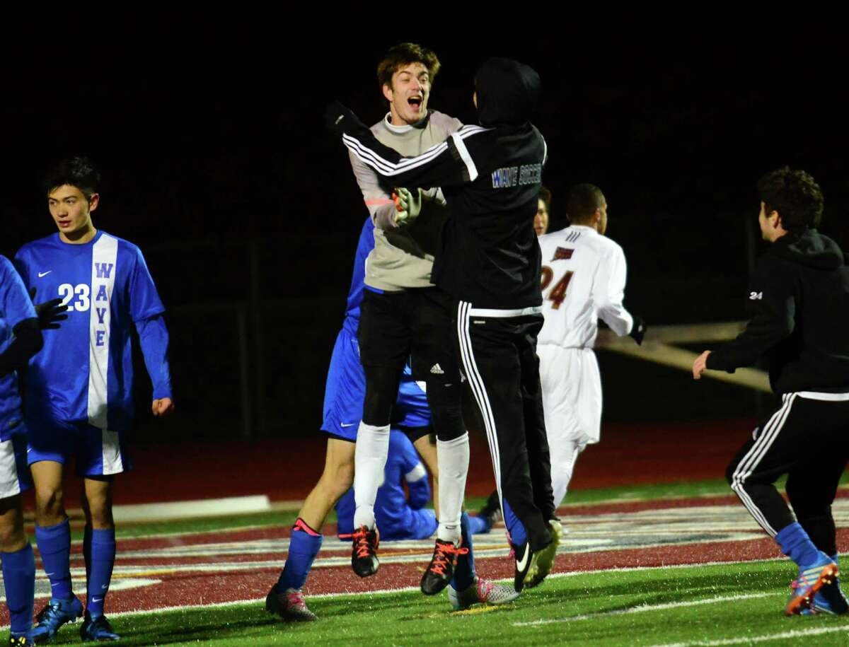 Darien goalie Liam Rischmann, left, with teammates after beating Farminton 1-0 in the Class LL boys soccer semifinals on Tuesday in Naugatuck.