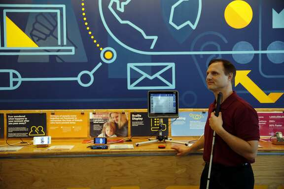 """Matt King, Facebook accessibility specialist, stands near the """"empathy lab"""" at Facebook headquarters in Menlo Park, California, on Tuesday, Nov. 17, 2015."""
