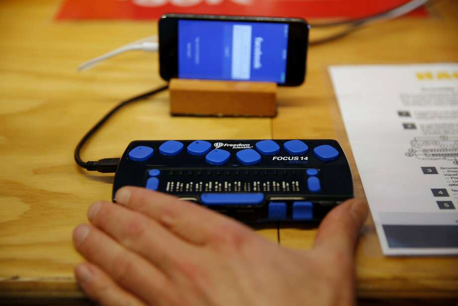"Matt King, Facebook accessibility specialist, demonstrates a braille reader hooked up to an iPhone with the Facebook app open at the ""empathy lab"" at Facebook headquarters in Menlo Park, California, on Tuesday, Nov. 17, 2015. Photo: Connor Radnovich, The Chronicle"