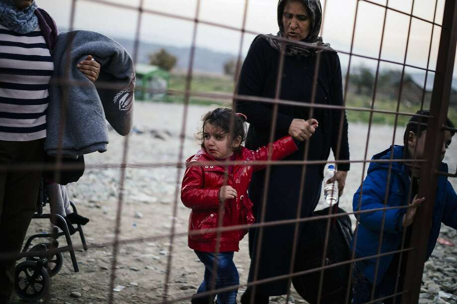 A woman and her crying child walk along with other migrants and refugees as they wait to enter a registration camp after crossing the Greek-Macedonian border near Gevgelija on November 17, 2015. More than 800,000 refugees and migrants have landed in Europe so far this year and more than 3,000 have died while crossing the Mediterranean in search of a new life in the world's largest economy. Photo: Dimitar Dilkoff, AFP / Getty Images