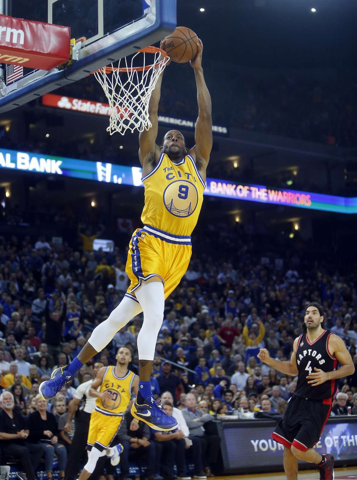 Golden State Warriors' Andre Iguodala dunks as Toronto Raptors' Luis Scola watches in 2nd quarter during NBA game at Oracle Arena in Oakland, Calif., on Tuesday, November 17, 2015.