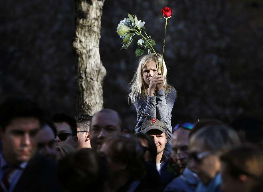 Neeley, 8, of Virginia, sits on her father's shoulders during a moment of silence that was part of a tribute and ceremony remembering victims of this weekend's Paris terrorist attacks at the 9/11 Memorial and Survivor Tree, right, Monday, Nov. 16, 2015, in New York. Photo: Kathy Willens, Associated Press