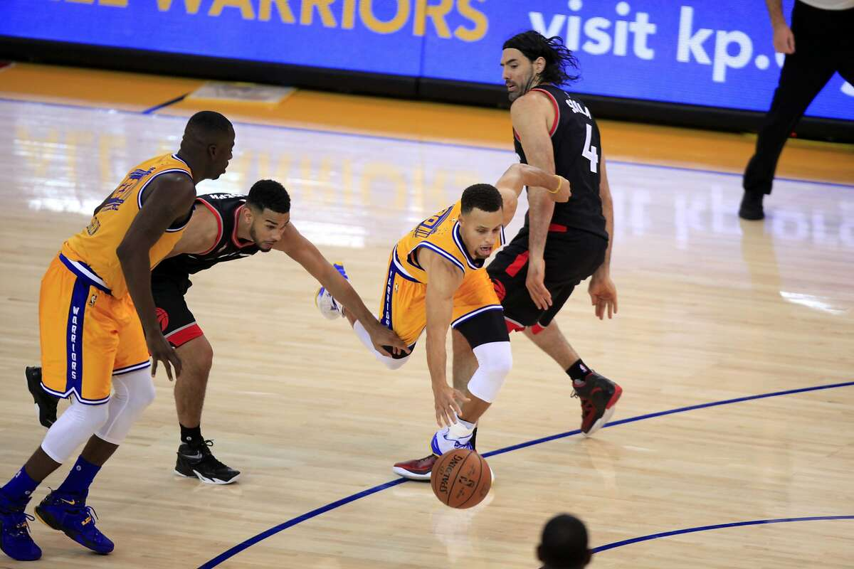 Stephen Curry gets fouled while dribbling the ball in the fourth quarter of a game between the Warriors and the Toronto Raptors in Oakland, California, on Tuesday, Nov. 17, 2015.