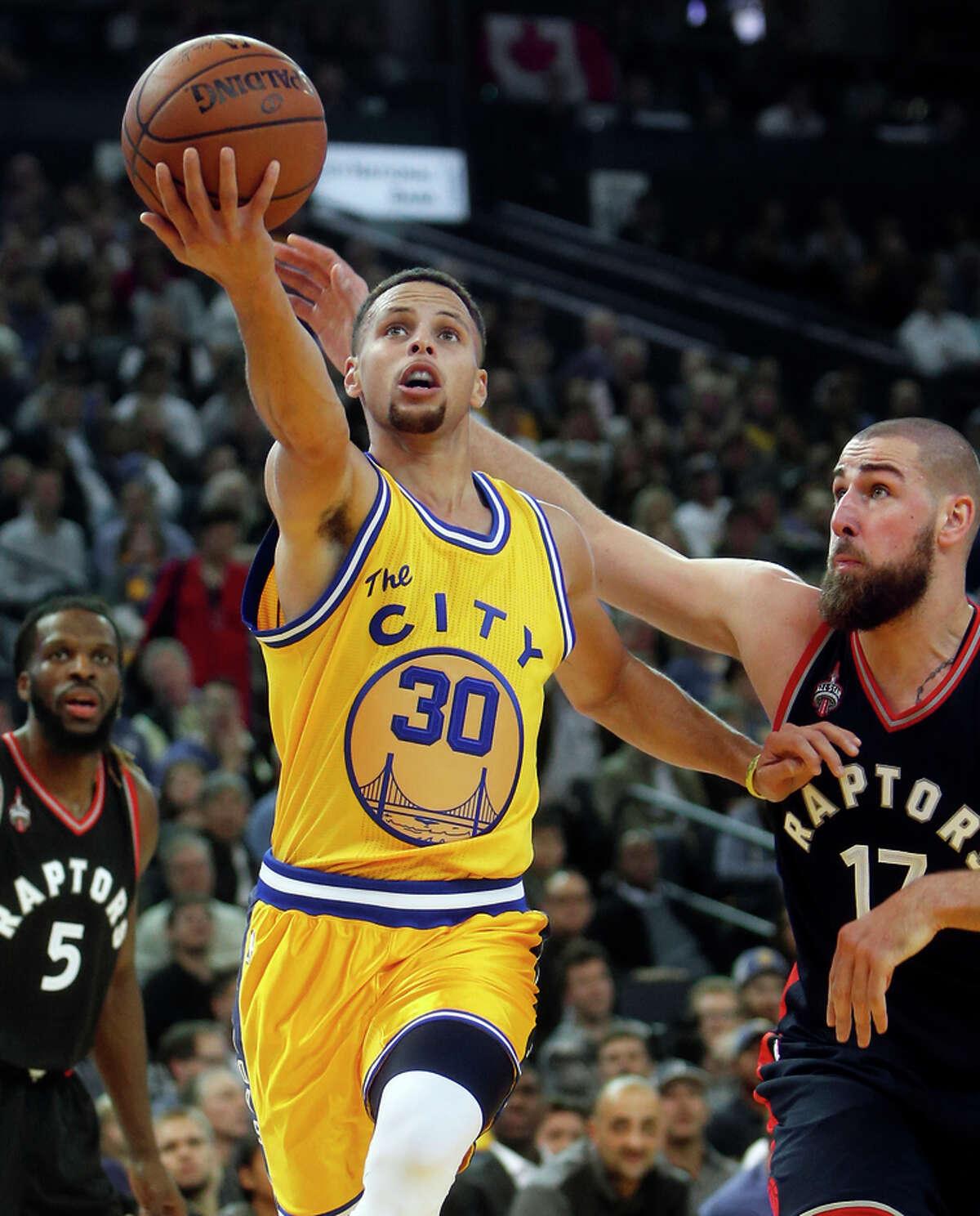 Warriors guard Stephen Curry scores past Toronto center Jonas Valanciunas in the second quarter.