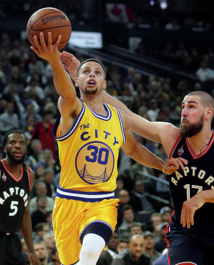 Warriors guard Stephen Curry scores past Toronto center Jonas Valanciunas in the second quarter. Photo: Scott Strazzante / The Chronicle / ONLINE_YES