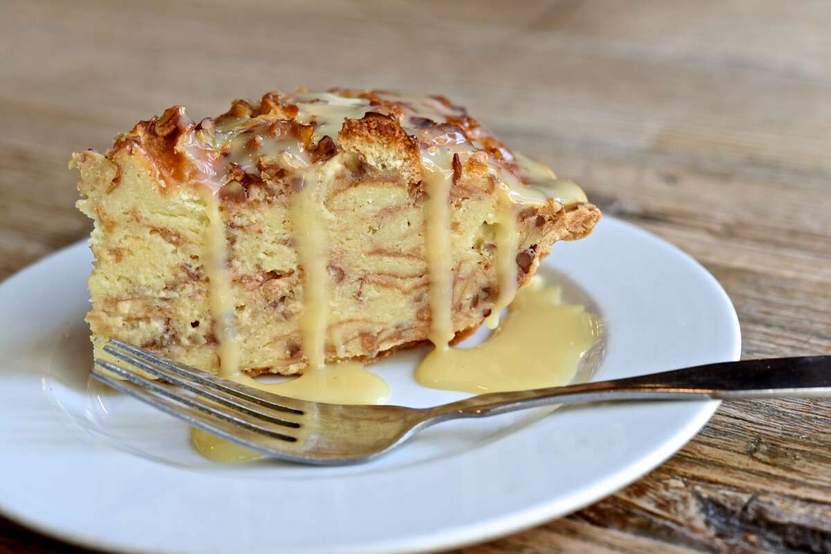 """Take your choice of a white chocolate sauce or a caramel sauce drizzle on this White Chocolate Bourbon Pecan Bread Pudding Pie. The price for a slice is $6.00 and $45.95 for a whole 10"""" pie. Find the nearest store at oohlalasweets.com."""