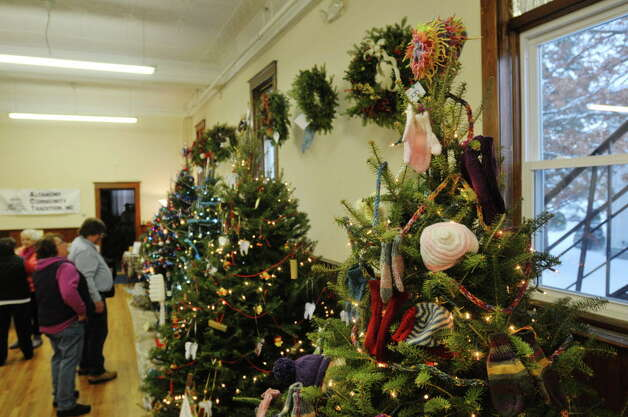 Visitors look over the decorated Christmas trees at the Masonic Hall during the Festival of Trees and Wreath Auction at the Altamont Victorian Holiday Celebration on Sunday, Dec. 15, 2013 in Altamont, NY.  The trees on display are decorated by organizations and businesses.   (Paul Buckowski / Times Union) Photo: PAUL BUCKOWSKI / 00024873A
