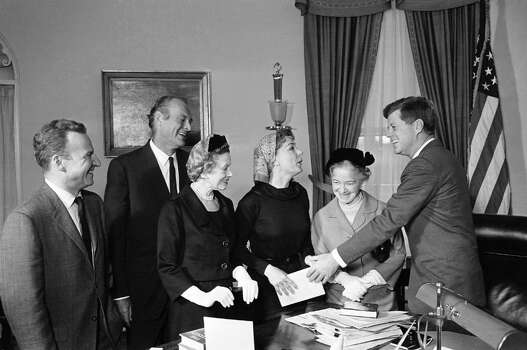 "In this Feb. 28, 1961 file photo, President John F. Kennedy listens to actress June Havoc, third from right, as he hands her a copy of his book, ""Strategy of Peace"" which he presented to her and Helen Hayes, center. Photo: AP File Photo / AP"