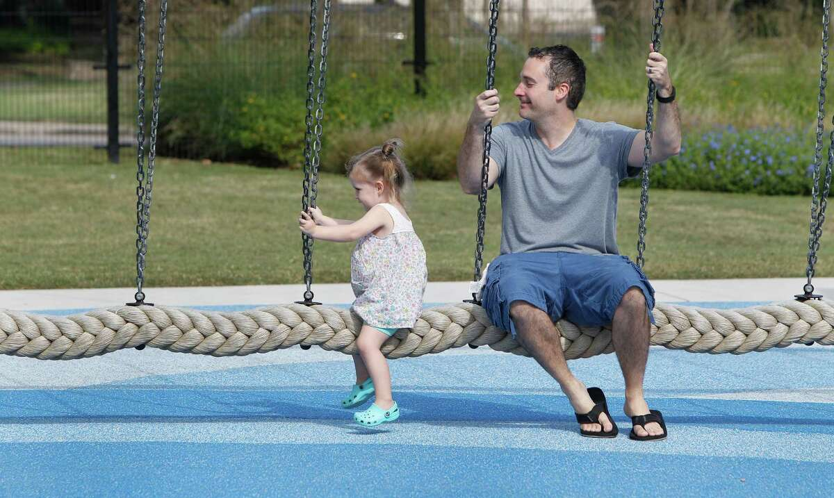 Travis Corgey swings with his 2 year-old daughter Zoe in Cinco Ranch's Exploration Park. Nature-themed parks are growing in master-planned communities.