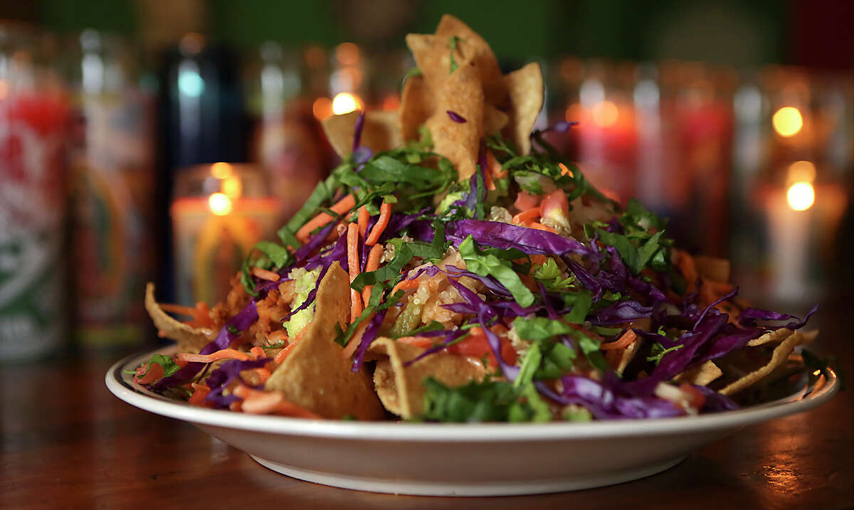 Vegan Nachos highlight housemade tortilla chips, which are topped with shredded carrots and cabbage, vegan queso, garbanzos in a spicy sauce and an avocado ranch dressing.