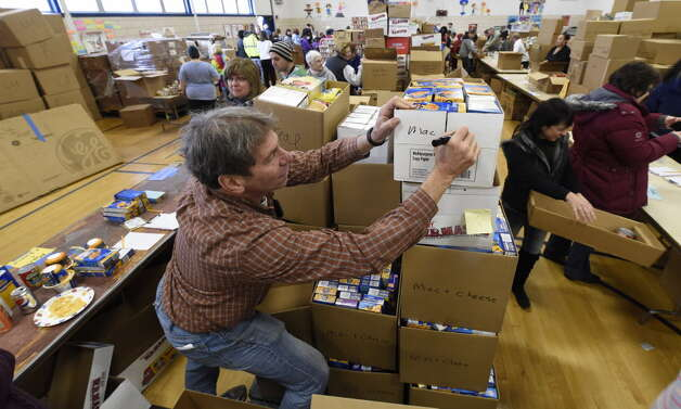 Concerned for the Hungry volunteer Larry Lewis sets up boxes of donated food for Thanksgiving on Nov. 21, 2014, at William C. Keane Elementary School in Schenectady. (Skip Dickstein/Times Union archive)