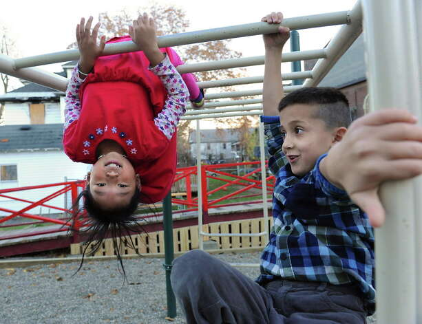 Ngameh of Albany originally from Thailand, 8, left, and Sehail Mohamad of Albany originally from Afghanistan, 7, play on the monkey bars on a playground during an after-school program for refugee children at the Refugee and Immigration Support Services of Emmaus (RISSE) classroom on Monday, Nov. 9, 2015 in Albany, N.Y. Ngameh goes by one name. (Lori Van Buren / Times Union) Photo: Lori Van Buren / 00034133A