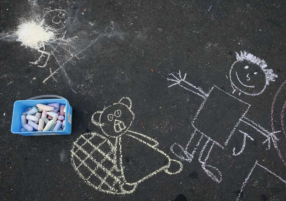 Chalk art decorates pavement outside the bus, a field trip and party rental converted into a classroom three days a week. Photo: Paul Chinn, The Chronicle