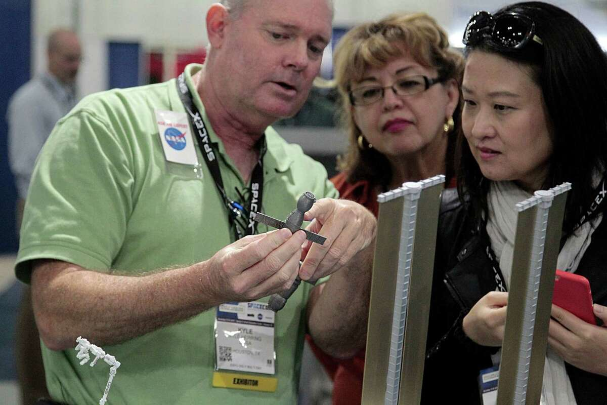 NASA's Kyle Herring left, discusses details of a Russian Soyuz capsule in front of a model of the International Space Station to Linda Liu right, as NASA's Rose Herrera center, looks on in the NASA booth during the Spacecom Space Commerce Conference and Exposition at George R. Brown Convention Center Wednesday, Nov. 18, 2015, in Houston. ( James Nielsen / Houston Chronicle )
