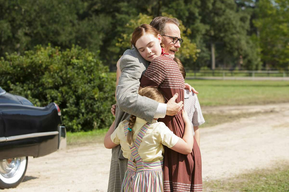 """This photo provided by Bleecker Street shows Bryan Cranston, right, as Dalton Trumbo, embracing his children, with Elle Fanning, left, as Niki Trumbo, in Jay Roach's """"Trumbo,"""" a Bleecker Street release. The movie opens in U.S. theaters on Friday, Nov. 6, 2015. (Hilary Bronwyn Gayle/Bleecker Street via AP)"""