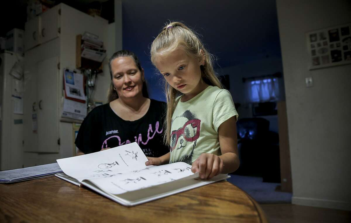 7-year-old Genevieve Callahan who has had two cochlear implants prepares her school materials to work with San Francisco speech-language pathologist/authority therapist Sayard Benvenuti via live streaming, at their home in Benicia, Calif., on Tues. November 17, 2015. Denee Callahan, (left) is always close by to help her daughter with her studies.