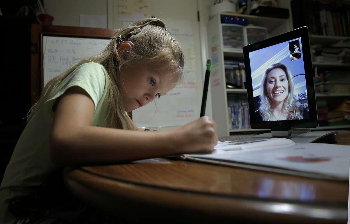 7-year-old Genevieve Callahan who has had two cochlear implants works with San Francisco speech-language pathologist/authority therapist Sayard Benvenuti via live streaming as they work together on her school homework at their home in Bencia, Calif ., on Tues. November 17, 2015.